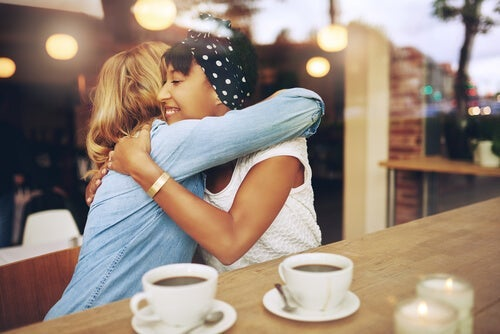 Two girlfriends hugging while having coffee.