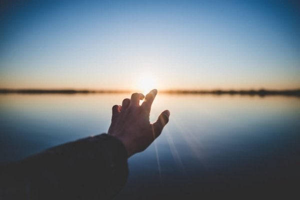 A person's hand reaching out towards a sunset over the water.