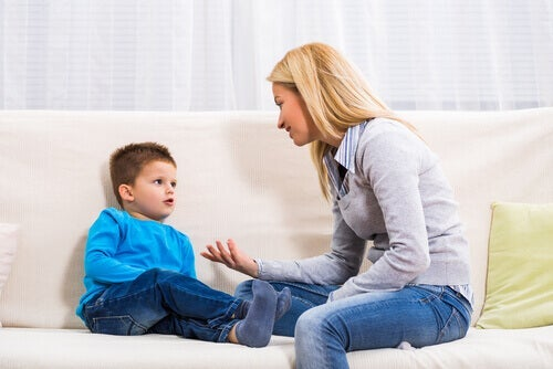 A mom sitting on the couch with her son, explaining something to him.