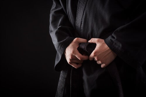 A person with their hands clasped around their martial arts belt.