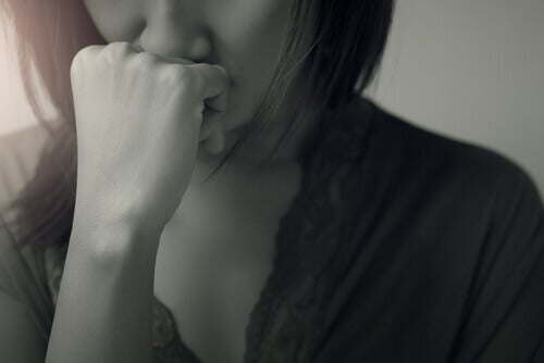 A person holding their hand under their nose, in thought.