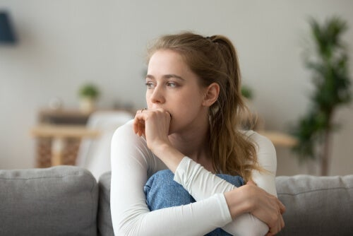 A woman sitting on the couch with her knees in her chest, looking thoughtful, or concerned.