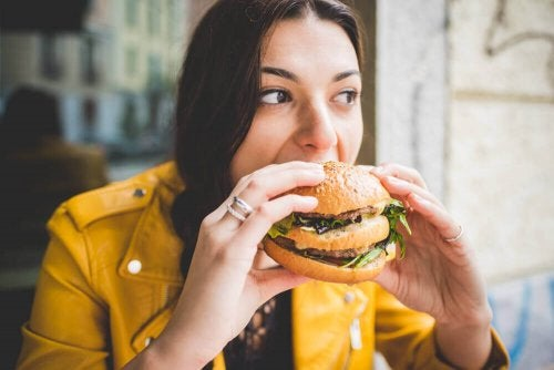 A woman eating a hamburger.