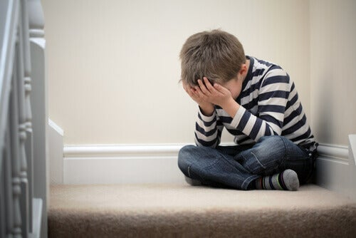 A boy sitting on the stairs in his home, crying.
