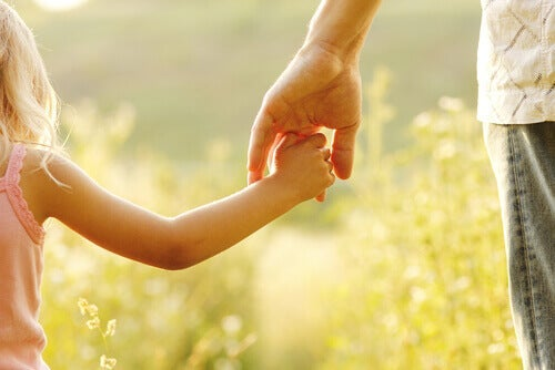 A child holding hands with their parent in a field.