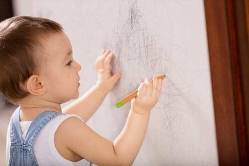 A boy drawing on a piece of paper.