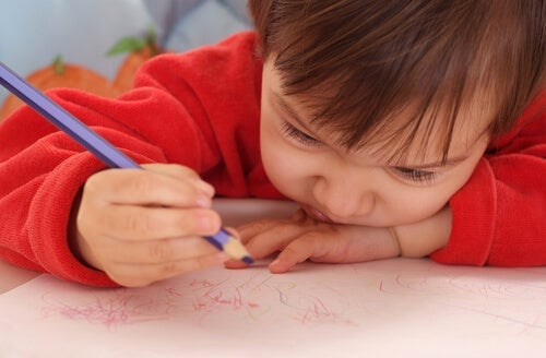 A child scribbling with a colored pencil.