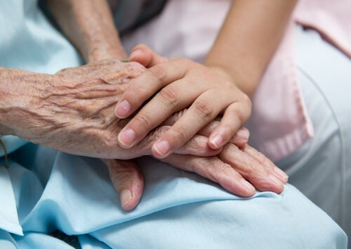A young person putting their hand over an elderly person's in a hospital.