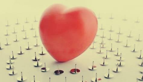 A heart balloon standing on the ground, surrounded by pins.