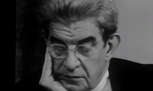 Jacques Lacan thinking with glasses on.
