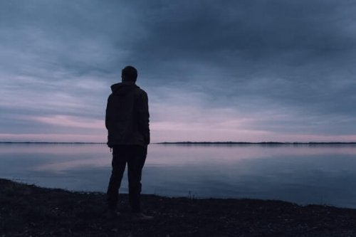 A sad man in front of a lake.