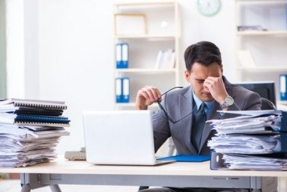 A stressed guy at work with piles of papers.