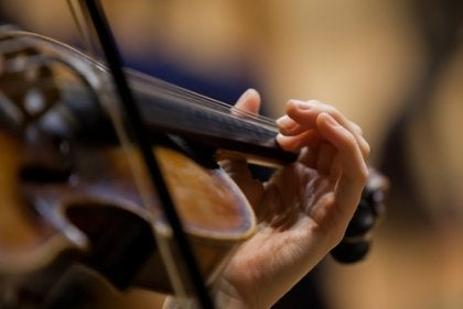 The hand of a violinist playing.