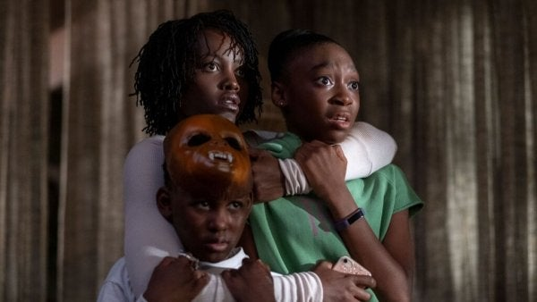 The mother in Us standing with her two kids in her arms, protecting them.