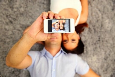A man taking a selfie of himself and a woman.