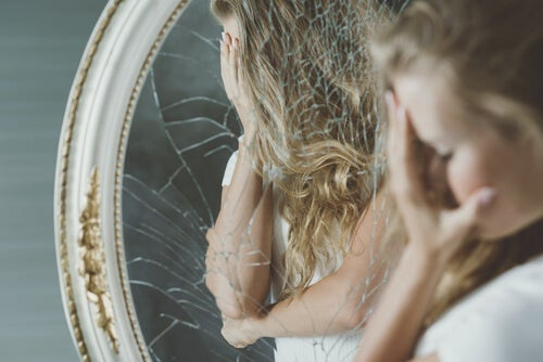 A woman in front of a broken mirror.