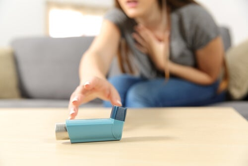A woman reaching for the inhaler.