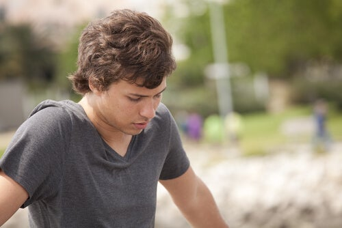 A teenage boy looking down.