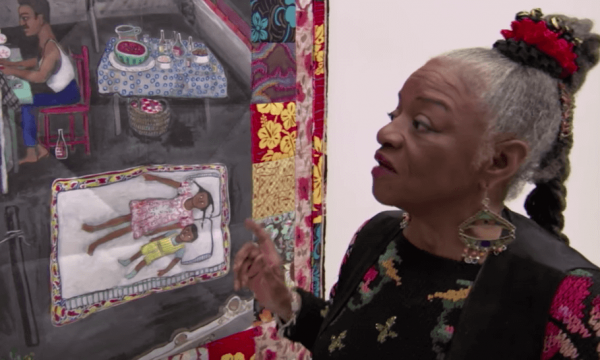 Faith Ringgold looking at some artwork.