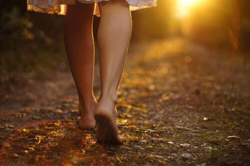 Someone seen from the calves down walking down a street barefoot.