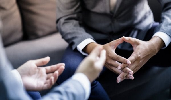A close-up showing two people's hands as they have a conversation.