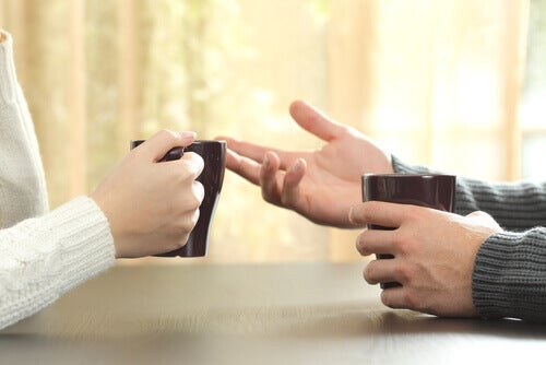 A close-up of two hands gesturing as people talk with coffee mugs in hand.