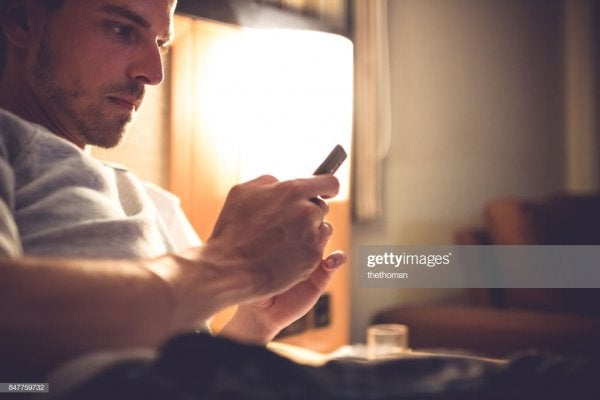 A man with his cellphone in bed.