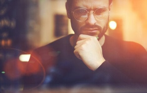A man in glasses with his hand on his chin, thinking deeply about something.