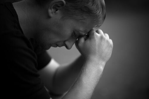 A man crying with his head in his hands.
