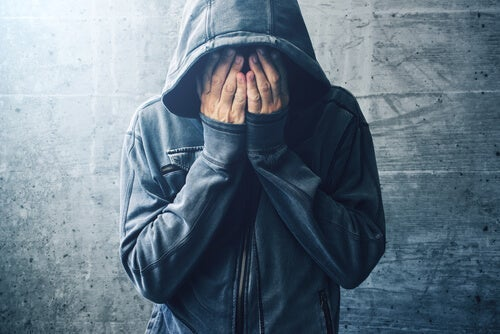 A person wearing a hoodie, crying into their hands.