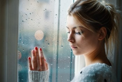 A sad woman with her hand on the window.