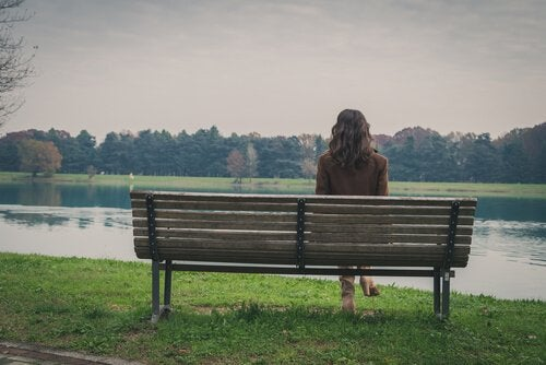 A woman sitting alone on a bench.