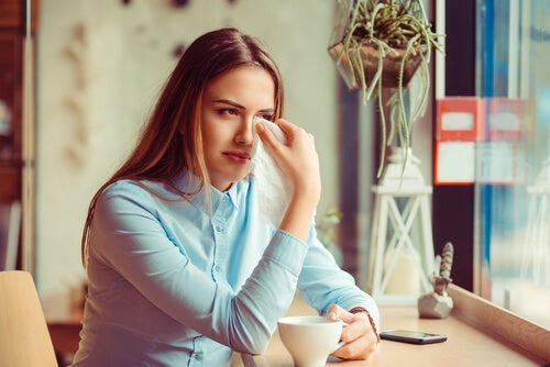 A woman crying at a coffee shop, wiping her eyes with a napkin.