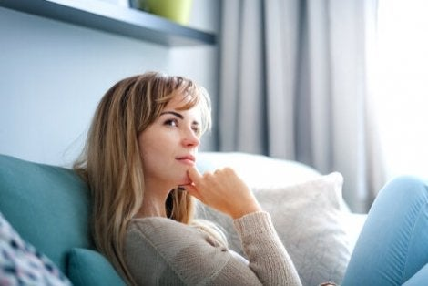 A woman sitting on the couch thinking, with her hand on her chin.