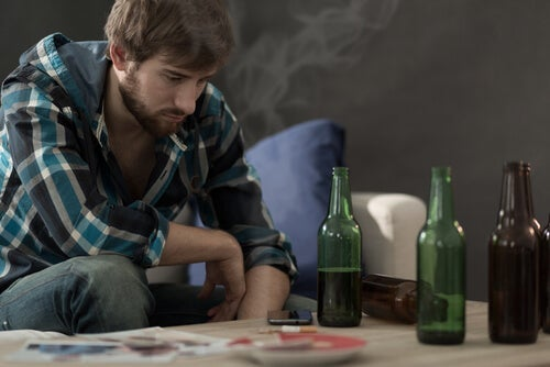 A man staring at bottle sof alcohol on a table.
