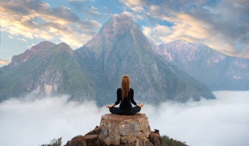 A person meditating on top of a mountain to deal with their mental fatigue.