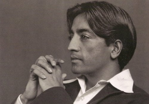 Jiddu Krishnamurti, crossing his hands and staring into the distance.