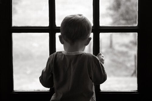A child looking out the window sadly.