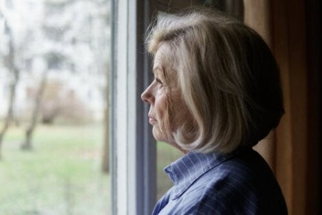 A bitter woman looking out the window thinking about this story about prejudice.