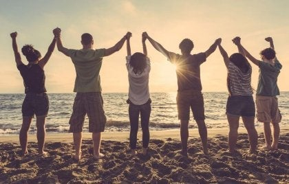 A group of friends holding hands on the beach.