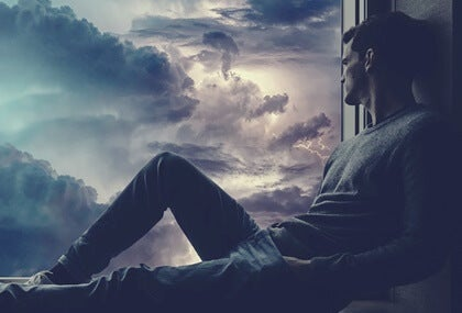 A guy looking out the window at a stormy sky.