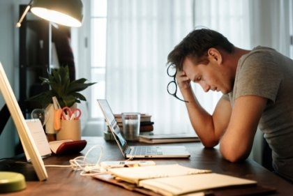 A guy with work-related fatigue at his desk.