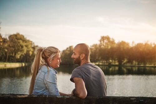 A man and a woman talking at the lake.
