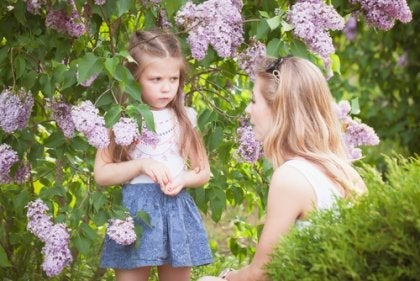 A mother and daughter next to a lilac bush.