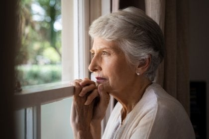 An older woman looking out the window.