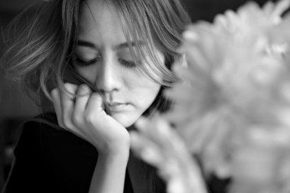A sad woman next to a flower.