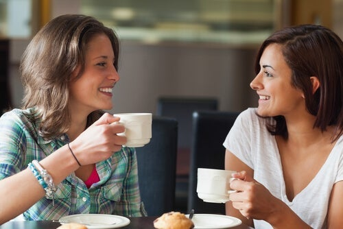 Two friends having coffee and smiling.