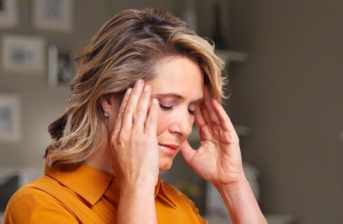 A woman with a headache putting her hands on her temples.