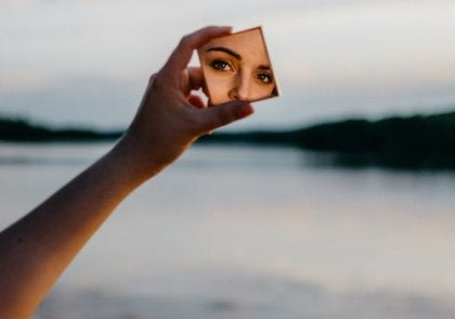 A woman looking at herself in a small square mirror.