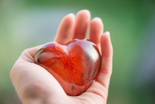 A person holding a heart made of glass.
